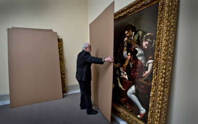 Jeff Harrison, chief curator removes the cardboard from this painting by Giovanni Battista Boncori inside the new Skylight Gallery.