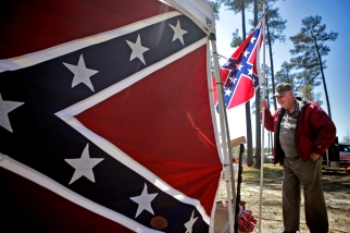 Sidney Lester holds a Confederate flag near the Virginia Flaggers display during the 66th annual Shad Planking Wednesday afternoon in Wakefield.