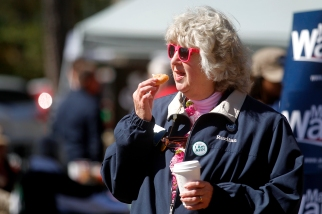 Sandra Hogge eats a piece of fish during the 66th annual Shad Planking Wednesday afternoon in Wakefield.