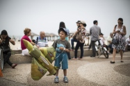 A young boy plays with a plane-shaped balloon on the beach in the Mediterranean sea as people wait for the military air show marking the 66th anniversary of Israel's independence to start on May 6, 2014 in Tel Aviv, Israel. (Photo by Ilia Yefimovich/Getty Images)