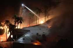 Firefighters spray water on a burning commercial structure at the Poinsettia fire, one of nine wildfires fueled by wind and record temperatures that erupted in San Diego County throughout the day, on May 14, 2014 in Carlsbad, California. Fire agencies throughout the state are scrambling to prepare for what is expected to be a dangerous year of wildfires in this third year of extreme drought in California. The Poinsettia fire has destroyed at least eight homes and severely damaged eight condos and two businesses. (Photo by David McNew/Getty Images)