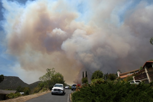 Smoke rise as the southeast flank of the Cocos fire bears down on houses near Del Dios Highway on May 15, 2014 near San Marcos, California. Fire agencies throughout the state are scrambling to prepare for what is expected to be a dangerous year of wildfires in this third year of extreme drought in California. (Photo by David McNew/Getty Images)
