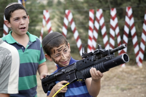 An Israeli boy plays with an M-16 rifle during a traditional military weapon display to mark the 66th anniversary of Israel's Independence at the West Bank settlement of Efrat on May 6, 2014 near the biblical city of Bethlehem. Israelis are marking Independence Day, celebrating the 66th year since the founding of the Jewish State in 1948 according to the Jewish calendar. AFP PHOTO/GALI TIBBONGALI TIBBON/AFP/Getty Images