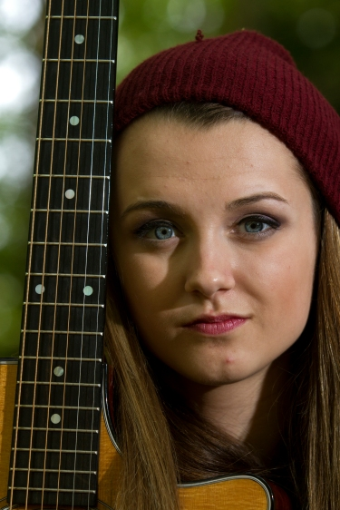 Bria Kelly sits with her guitar in her backyard on Wednesday. Kelly returned to Smithfield last week and is turning her focus to graduating from high school.