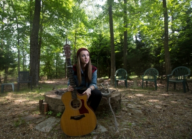 """Smithfield's Bria Kelly, 18, sits with her guitar in her backyard on Wednesday afternoon. Kelly made it to the final 10 contestants on NBC's """"The Voice"""" out of 70,000 people who initially auditioned this season."""