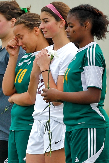 Bethel's Hailey Koger, left, and Brandi Jennings, right, pause for a moment of silence with Poquoson's Camille Freeman, center, as they remember Arnise Scott before the start of Wednesday's game at Poquoson.