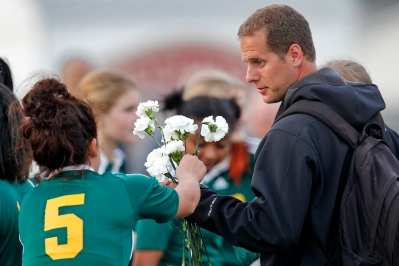 Bethel coach Steve Midlik, right, hands a flower to Karen Alvarado, left, that were given to the team by Poquoson players to remember Arnise Scott during Wednesday's game at Poquoson.