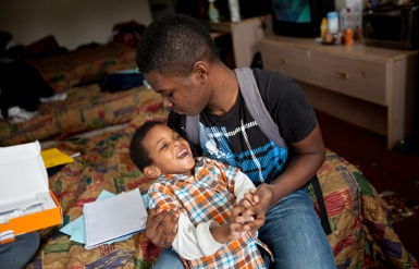 Tim, 4, and Terrance, 15, play on the bed after arriving home from school on March 15. (Photo by Kaitlin McKeown)