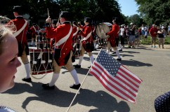 Gracie Robertson watches as the Colonial Williamsburg Fifes and Drums parade down Duke of Gloucester Street Monday during a ceremony honoring those killed in the American Revolution. (Photo By Rob Ostermaier)