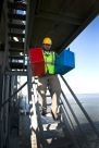Biologist Jake McClain from The College of WIlliam and Mary carries transport boxes holding Peregrine falcon chicks from the top of the James River Bridge north tower.
