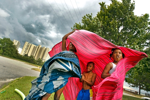 Jacquela Wynn, left, Zyion Jones, center, and Serenity Jones attempt to take cover underneath a blanket as high winds, rain and storm clouds approach Huntington Beach Thursday. (Photo by Jonathon Gruenke)