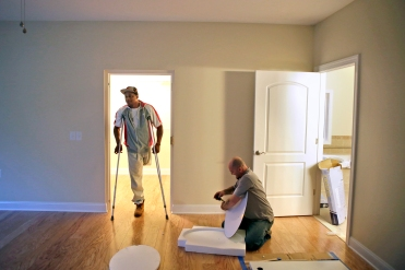 This photograph of Johnathan Jackson in his new home won first place in the lifestyle It was one of the entry category. Johnathan Jackson, left, talks with Tom Thorpe as he completes the finishing touches on the master bedroom inside Jackson's newly built home Thursday evening. Jackson lost his leg in Afghanistan after doctors say he was exposed to an unknown toxin. Homes for Our Troops built Jackson a house and he take the keys to the new home on Friday. (Photo by Jonathon Gruenke)