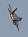 Flames pour from the engines of an F-22 Raptor as the fighter makes a tight turn that causes vapor to form on its wings during a flight demonstration of its capabilities at Langley Air Force Base.
