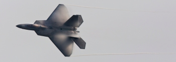 Vapor forms on the wings of an F-22 Raptor as it conducts a high speed turn during a flight demonstration of its capabilities at Langley Air Force Base.