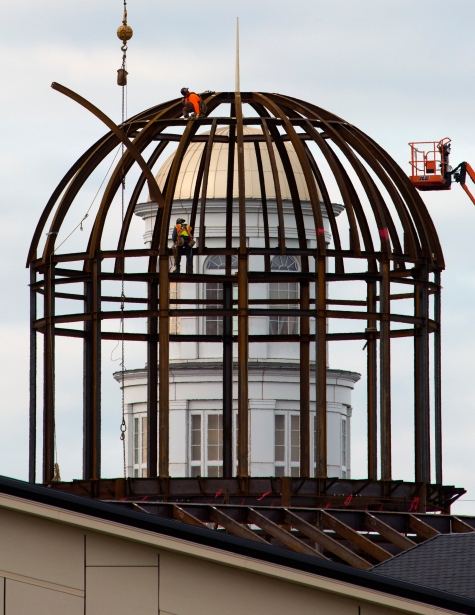 The Trible Library shows through the top of the Student Success Center as workers attach one of the few remaining steel beams to the dome of the structure Friday morning.