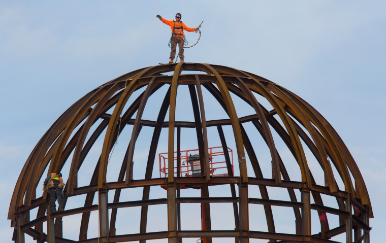 """""""I'm on the top of the world,"""" yells a steel worker after he and another steel worker attached one of the final steel ribs on the dome of the Student Success Center at Christopher Newport University Friday morning."""