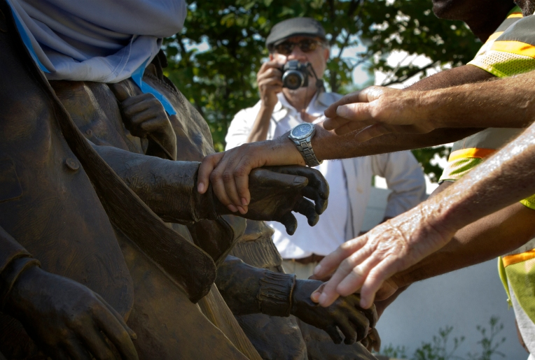 """Workers grasp statue hands from the """"The Unfinished March"""" as artist Ed Hamilton records the installation process Tuesday at Martin Luther King, Jr.  Plaza in Newport News."""