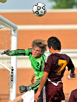 Kellam goalie Zach Ryan, left, turns around and looks for the ball as Warwick's Adolfo Figueroa-Hernandez, right, attempts to head it during Tuesday's first round of 5A South soccer tournament at Powhatan Sports Complex.
