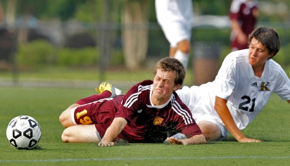 Warwick's Christian Murphy falls to the ground after a slide tackle from Kellam's Bryce Reed during Tuesday's first round of 5A South soccer tournament at Powhatan Sports Complex.
