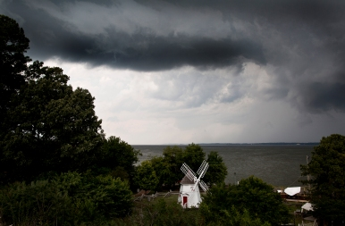 A cold front moves across the York River Thursday afternoon bringing clouds filled with rain, lightning and high wind. The York River Bridge, the Watermen's Museum buildings and windmill are shown in the foreground. (Photo by Joe Fudge)