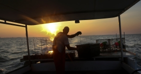 Tim Lindsay, Jr. prepares crab pots aboard the Miss Nina as the sun rises over the James River early Wednesday morning.