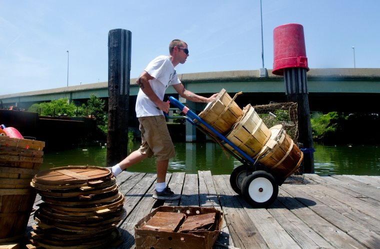 Tim Lindsay, Jr. wheels baskets of harvested crabs up the dock at the Newport News Small Boat Harbor after a morning of crabbing on Wednesday.
