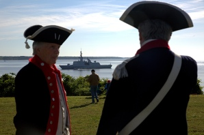 Two men dressed in Virginia/American Revolutionary War uniforms stand near the Yorktown Monument as the French frigate La Fayette rests in the York River. (Photo by Joe Fudge)