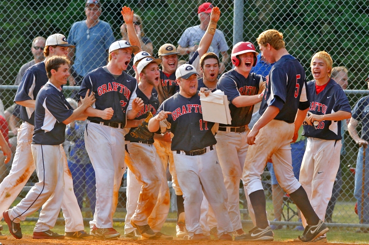 Grafton players celebrate as Evan Sperling, 5, crosses home plate after hitting a home run during Wednesday's 4A South region baseball semifinals against Kings Fork.