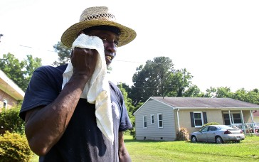 Caston Campbell takes a break from yard work Tuesday afternoon as temperatures reach near 100 dregrees on the Peninsula. (Photo by Rob Ostermaier)