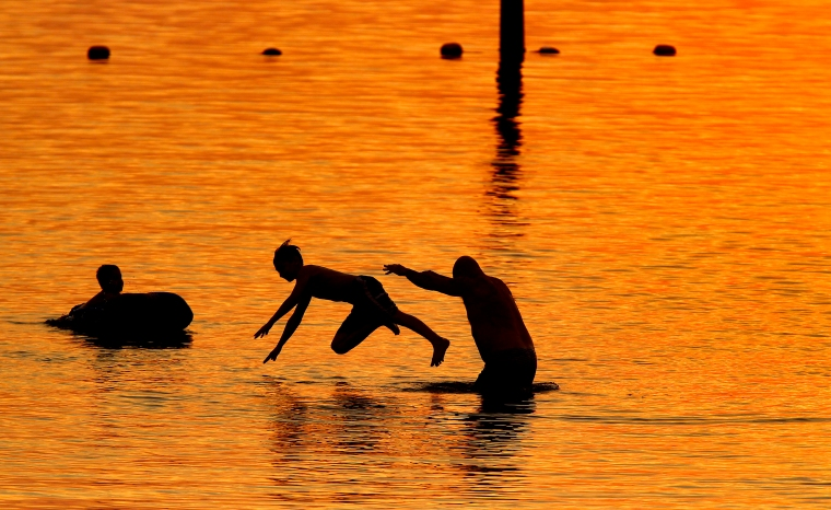 Shawn Allen, right, throws his eleven-year-old son, Josh, into the water as brother Chris watches as the sun sets at Huntington Beach Tuesday evening. (Photo by Jonathon Gruenke)