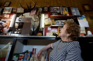 Stella admires a wall filled with family photos and memorabilia from her spot behind the counter at Tracy's Restaurant. Over the past several weeks, Stella and her children have worked to sort through and clean out personal items from the restaurant ahead of its closing.