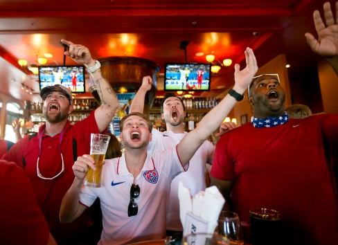 """Tim Whitlock, Connor Stevenson, Everette Johnson and River Cypress react to a play while watching the first half of the United States versus Ghana World Cup game on Monday at Park Lane Tavern in Hampton. Stevenson described the game watching atmosphere as festive but tense. """"It's pretty much the best time you can ever have but it's also nerve-wracking,"""" he said. """"Everybody supports America, and that's what it's about. We're all coming together for it."""""""