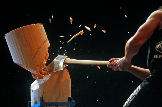 Sam Mulhollan-Wong cuts through a piece of wood with his axe during the standing block chop event of Friday's Stihl Timbersports collegiate championship qualifying rounds at Norfolk Scope Arena.