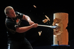 Joshua Wilson cuts through a piece of wood with his axe during the standing block chop event of Friday's Stihl Timbersports collegiate championship qualifying rounds at Norfolk Scope Arena.