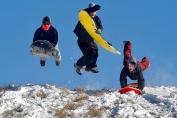 From left Spencer Satchell, 16, Carter Ashley, 14, and Nick Long, 15, jump into the air to gain speed while sledding down a hill at Riverview Farm Park in Newport News Wednesday morning.