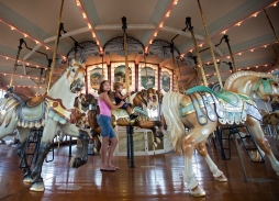 Anessa Hill, 12, rides the Hampton Carousel with her brother, Vasani Henderson, 1, on Monday afternoon in downtown Hampton. (Photo by Kaitlin McKeown)