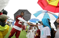After borrowing his umbrella Redskins safety Ryan Clark gives Deryion Willliams a fist-bump Thursday during the first day of training camp. (Photo by Rob Ostermaier)