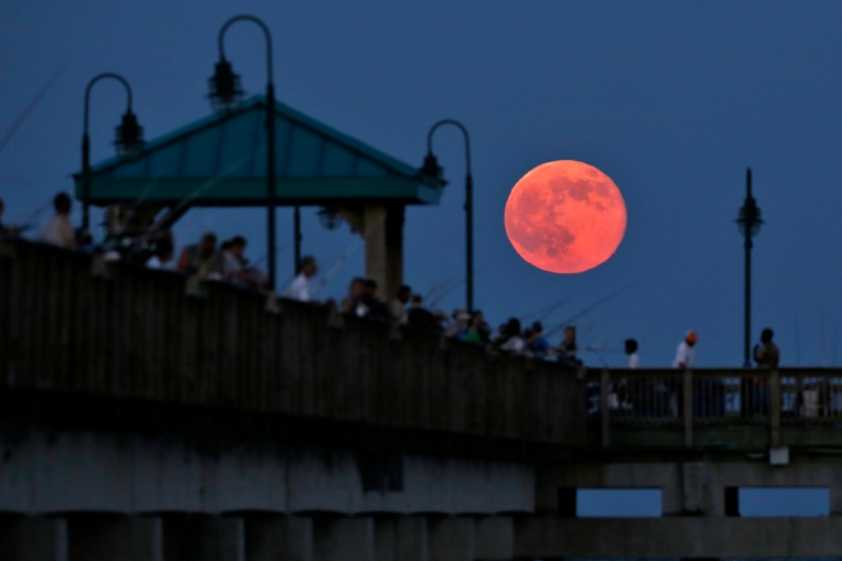 A super moon rises over the Buckroe Fishing Pier Saturday evening.