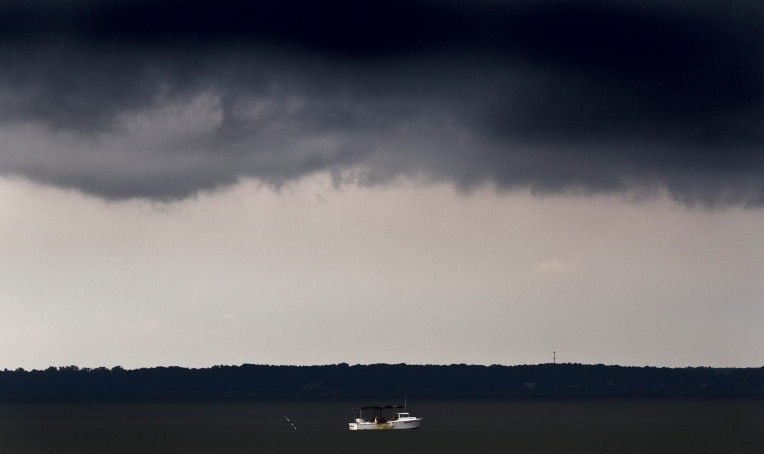 A waterman works the waters of the James River beneath threatening skies early Thursday morning. Storms in the front spawned a tornado that later struck the eastern shore of Virginia. (Photo by Joe Fudge)