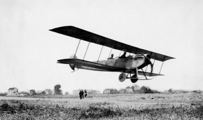 """The Curtiss JN4 """"Jenny"""" ranked among the most famous and well-recognized early airplanes, especially after it became the aircraft of choice for dare-devil pilots performing in barnstorming demonstrations during the 1920s. This 1916 photo shows it flying over the Curtiss Flying School airstrip in Newport News with spectators and houses along Ivy Avenue in the background. (Courtesy of Kurt P. Wheaton)"""