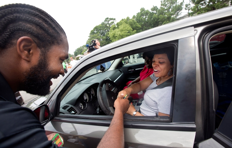 New England Patriots linebacker Jerod Mayo, a Kecoughtan High School graduate, gives a Food Lion gift card to a woman during a food donation event at Food Lion on Nickerson Boulevard in Hampton on Wednesday.