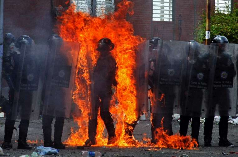 A riot policeman is set on fire by a molotov cocktail thrown by a small group of anti-government protesters during clashes in San Cristobal, Venezuela on August 25, 2014. The demonstrators protested against the control of the fingerprints to buy food, the raise in the public transportation costs, the lack of safety, the shortage of goods and the closure of the border with Colombia.   AFP PHOTO/GEORGE CASTELLANOS