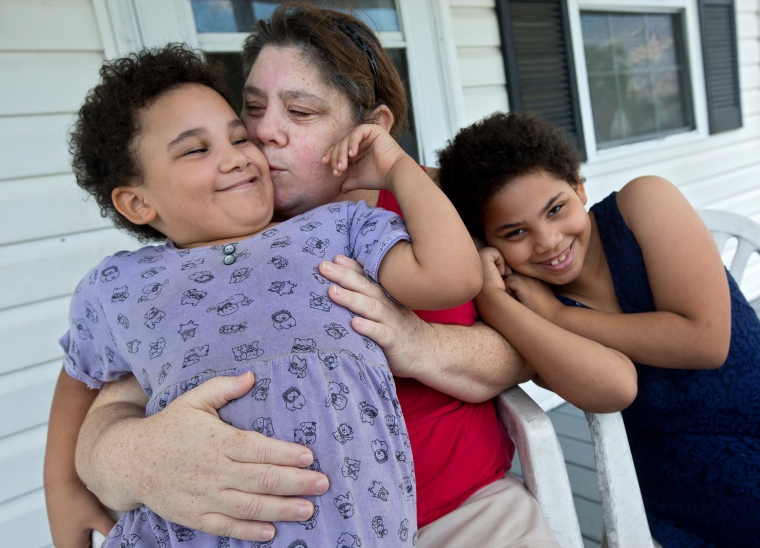 Christine Hadley, center, embraces her daughters Diana, 5, and Bella, 7, on the front porch of their home in Hampton.