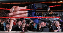 Spectators react as Chris Blanton, Lil Show, flies out of the ring at Cozzy's Comedy Club during a wrestling performance Wednesday evening. (Photo by Jonathon Gruenke)
