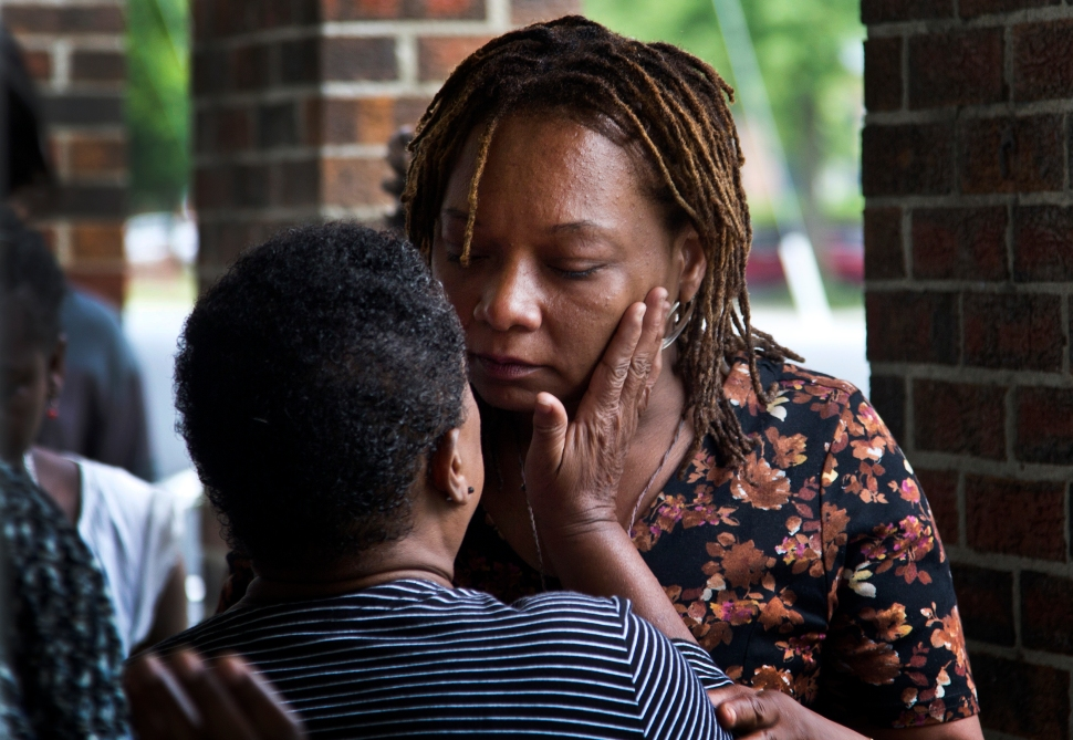 """Dawn Rashko is grieving the death of her son who had ties to the """"Bloods"""" street gang. Joel Rashko, 24, was shot in the head while watching a baseball game in a park Queens New York on May 10. Rashko and his brother Julien 23 are affiliated with the """"Bloods"""" street gang in Newport News. Here,  a friend wipes away her tears outside the funeral home. (Photo by Joe Fudge)"""