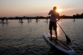 Weston Hanna paddles in the waters near Whitehouse Cove Marina in Poquoson amongst a group of other paddle boarders during a recent Tuesday evening. Every Tuesday evening and Saturday morning, Paddle 757 offers a paddle board fitness class that teaches strength training exercises and basic yoga poses to participants.