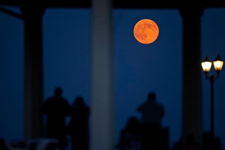 Spectators watch from a gazebo as a super moon rises over Fort Monroe Sunday evening. (Photo by Jonathon Gruenke)