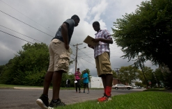 Terry Lassiter, left, speaks with Malik Spencer as a part of the Newport News Department of Human Services TOP program as Armon Tyler and Cameron Bozeman look on from the street on Monday afternoon in Southeast Newport News. (Photo by Kaitlin McKeown)