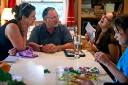 Patti Minium Moonis, left, and husband Mike Moonis, center, laugh while looking through a photo album with daughter Kathryn Minium on Thursday afternoon. (Photo by Jonathon Gruenke)