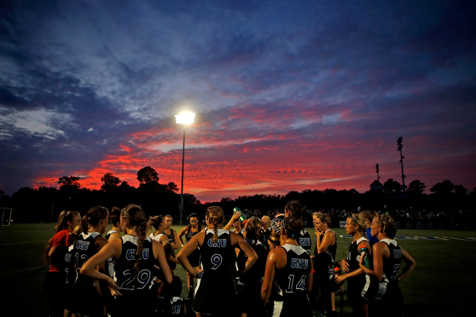 Christopher Newport University field hockey players listen their coach at halftime as the sun begins to set during Wednesday's against Lynchburg College. 4th ranked CNU went on to defeat Lynchburg 3-0.